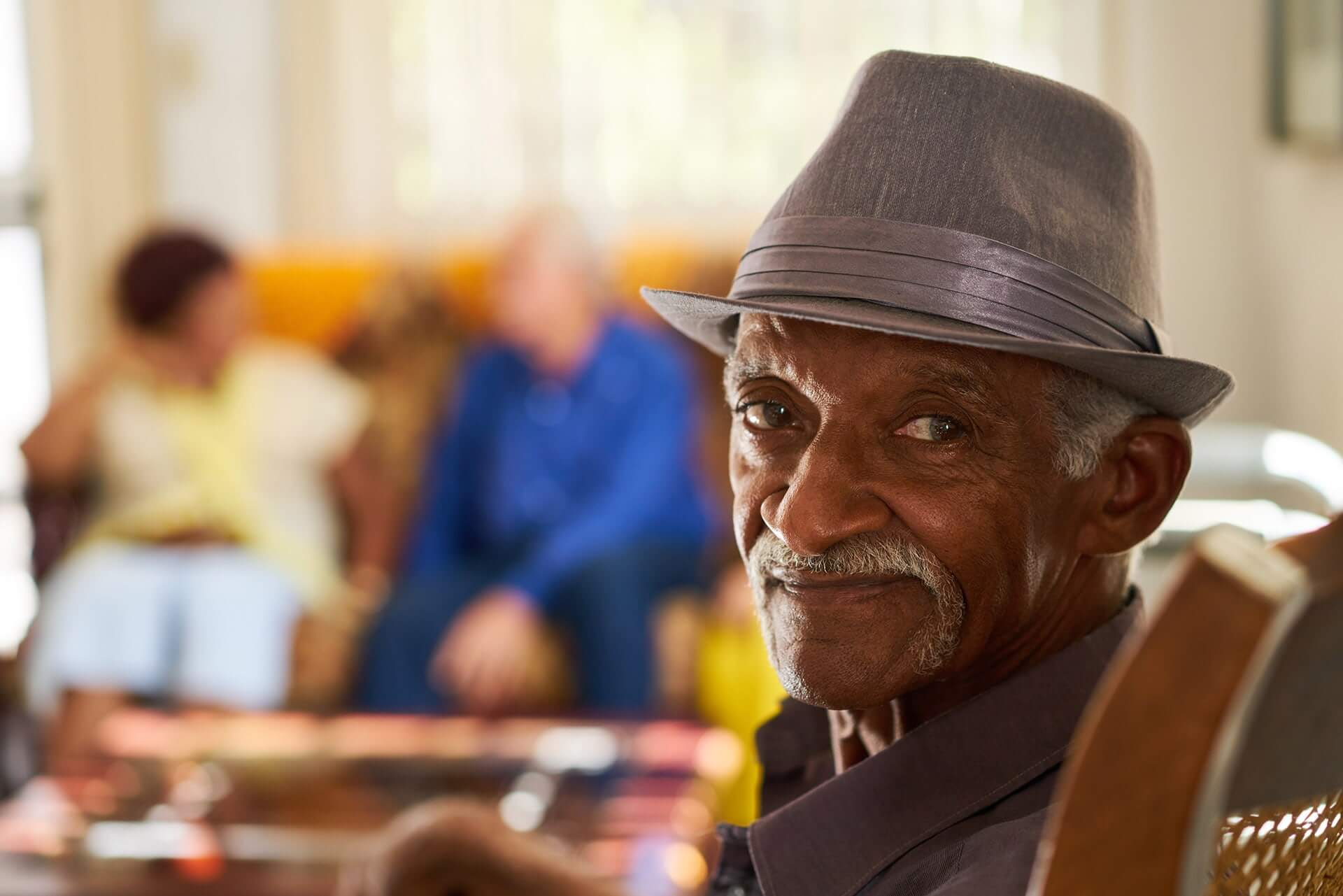 senior black man with hat looking at camera in P7EZM5E min 1