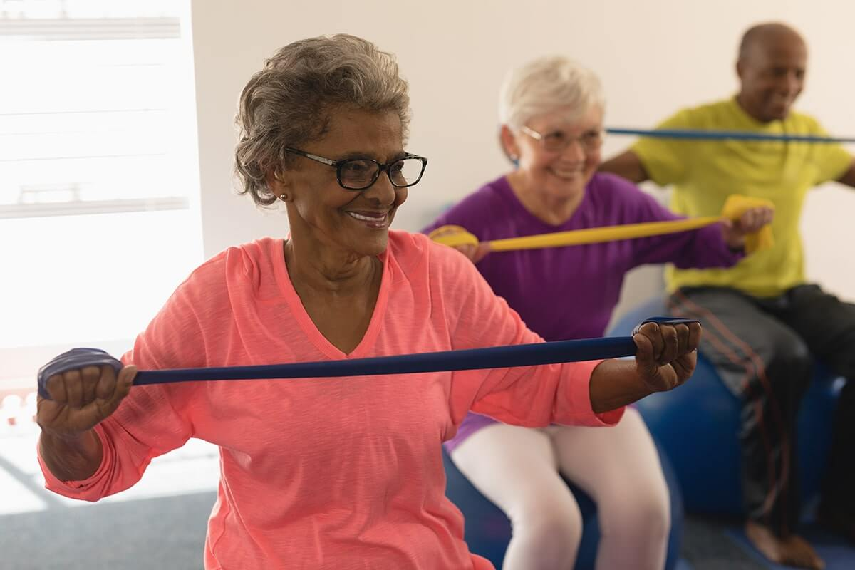 happy senior woman exercising with resistance New York