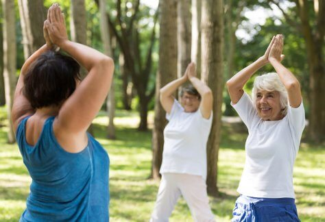 women doing yoga in a park P9AL75V tinified