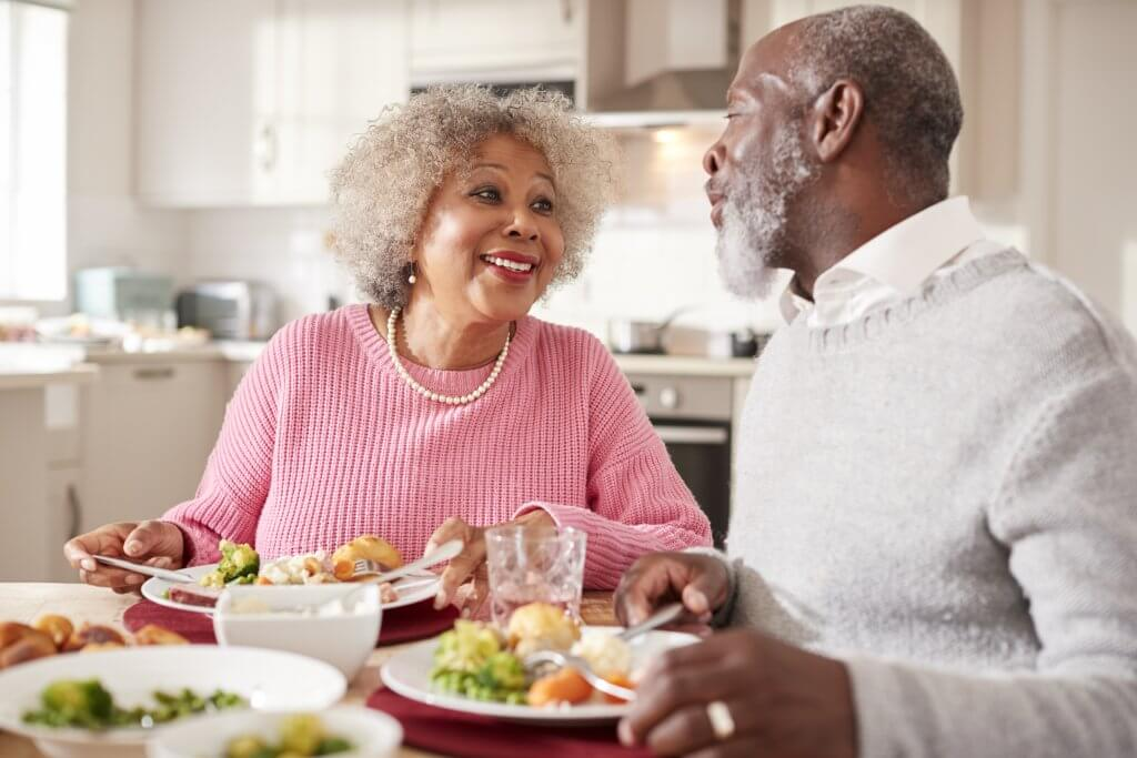 senior black couple smiling to each other as they 7N2GF3X
